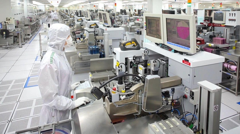 Ein Mitglied des Micron Produktionsteams trägt eine spezielle Haube, einen Kittel und eine Maske, um den Reinraum partikelfrei zu halten