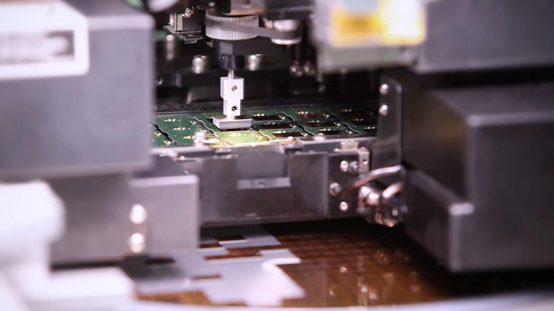 Eine Maschine entnimmt einen Chip aus dem Speiser und setzt ihn auf die Leiterplatine