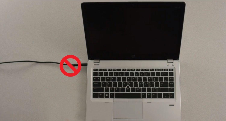 Ein Verbotszeichen auf der Oberseite eines Laptop-Netzkabels, das anzeigt, dass das Netzkabel vor der Installation entfernt werden sollte