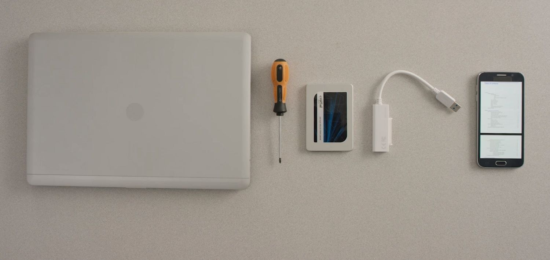 Ein Laptop, Crucial SSD, Schraubenzieher und die Bedienungsanleitung des Computers auf einem Handy sind auf einem Schreibtisch ausgelegt