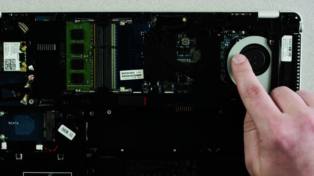Person, die eine unlackierte Metalloberfläche in einem Laptop berührt, um statische Elektrizität zu entladen