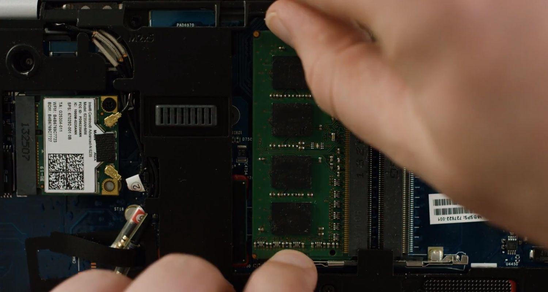 Person, die ein RAM-Speichermodul aus einem Laptop entfernt