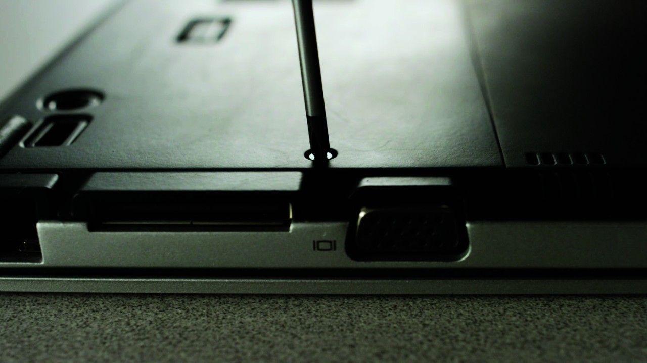 Schraubenzieher löst die Schraube an der Rückseite des Laptops