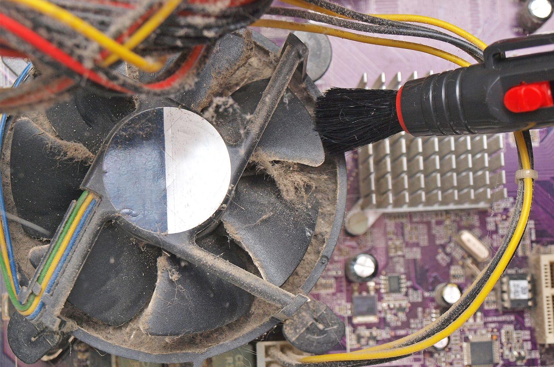 Kleine Bürste entfernt Staub und Flusen aus dem freigelegten Lüfter eines Desktop-Computers