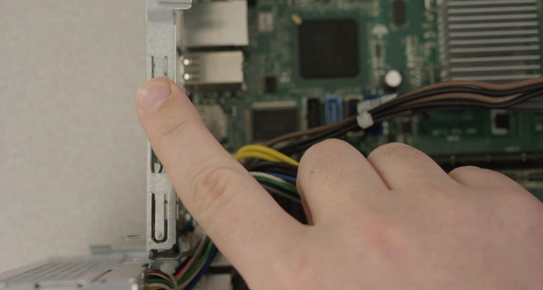 Finger einer Person, die eine unlackierte Metalloberfläche in einem Computer berührt, um statische Elektrizität zu entladen