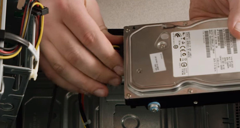 Person, die Kabel vom Speicherlaufwerk eines Desktop-Computers trennt